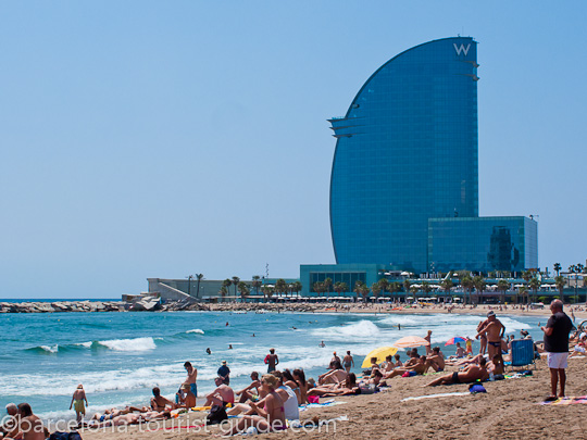 Barceloneta Beach In Barcelona The Famous W Hotel Looking Like A Giant Sail Against Blue Sky