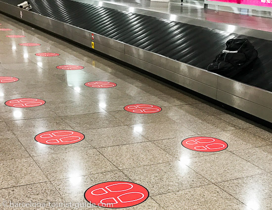 Safety distance stickers at Barcelona airport luggage claim